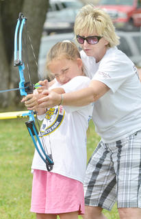 They learned about fishing, hunting and shooting and got some exercise along the way. More than 1,400 children attended the annual Kids Outdoor Day events at Green River Lake State Park on Saturday. Including adults and workers, about 2,800 pitched in to make the event a success. Bonnie Webster of Mt. Roberts Baptist Church helps Megan Settles of Greensburg learn to shoot a bow and arrow.