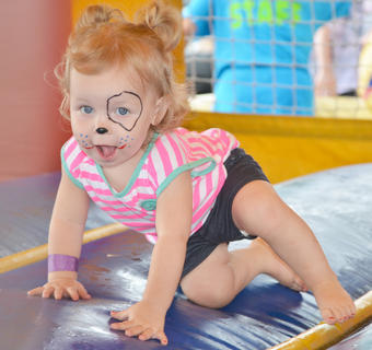 Aubri Dobson, 18 months, of Campbellsville, isn't quite sure what to do in the bouncy house at the Family Fun Zone.