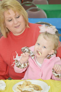 Taylor Houk of Campbellsville takes a bite of her pancake as her grandmother, Denise Glanzer, holds her.