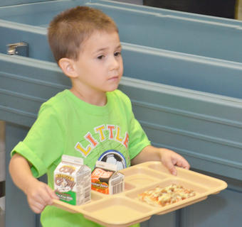 Campbellsville Elementary School kindergartener Joshua Heseman takes his breakfast tray to the cashier. This year, all Campbellsville students will eat breakfast and lunch for free.