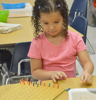 Campbellsville Elementary School kindergartener Madison Brown plays with a game before the school day starts.