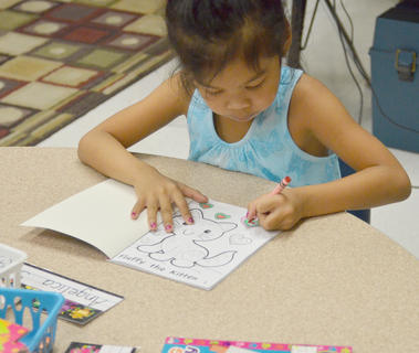 Campbellsville Elementary School kindergartener Angelica Seng colors a kitten as she waits for the school day to start.