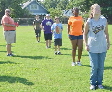 CHS director of bands Zach Shelton, at left, instructs his marching band members during a drill at band camp on Tuesday.