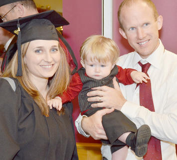 Miranda Kellum, of Depauw, Ind., at left, poses for a photo with her family before she receives her master's degree in marriage and family counseling. At right is Kellum's husband, Jim, holding their son Finn, 10 months.