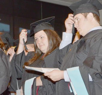 Charity Powell of Brandenburg, at left, and Christopher Price of Campbellsville turn their tassels as they graduate on Friday night. They received master's degrees in marriage and family counseling.