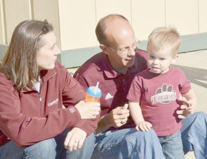 Rusty Watkins, who serves as coordinator of summer camps and conferences at Campbellsville University, sits with his wife, Megan, and their son, Caleb, as they wait for Saturday's Homecoming parade to begin.