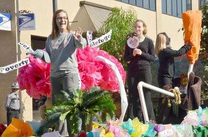 Members of the S.W.I.T.C.H., Social Works in Touch Can Help, Club at CU wave to the crowd from their float.
