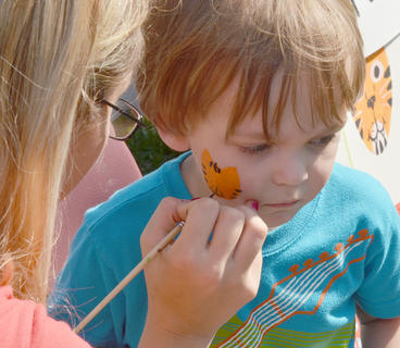 Brendan Martin, 2, of Campbellsville, gets a tiger painted on his face at Saturday's Homecoming festival.