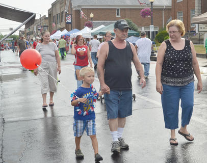 From left, Tyler, 3, Dennis and Anita Haulk, all of Campbellsville, walk down Main Street on Tuesday afternoon.