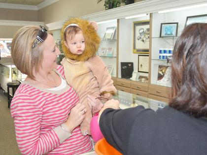 A lion trick-or-treater isn't so sure about getting candy at Tucker Diamonds and Gold.