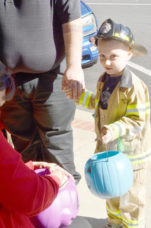 Fireman Björn Hartsock, 4, trick-or-treats at Mitchell's Men's Wear.