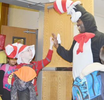 With colorful wigs and decorated hats, orange mustaches and badges proclaiming themselves Things 1 and 2, the students squeal as the mean Mr. Grinch comes near. The Cat in the Hat isn't far away, however, and has come to save the day. In honor of Dr. Seuss' birthday on Saturday, Campbellsville and Taylor County elementary schools celebrated last week with special dress-up days, reading and other events. More photos from the week will be published soon on the Education Page. Students at TCES give The Cat in the Hat a high-five.