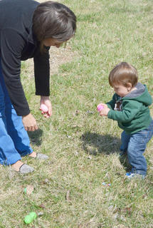 Zephaniah Dye, 13 months old, looks to see what's inside an egg he found on Saturday at a home in Holly Brook Subdivision, while his mother, Ahdazsa, of Campbellsville, looks on.