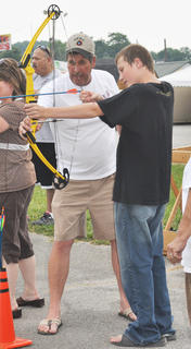 Christian Binkley shows Christian Binkley the proper way to hold a bow and arrow.