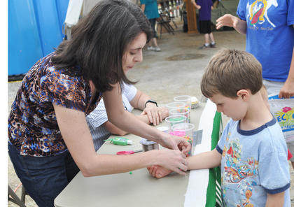 Amanda Sublett, County Extension Agent for 4-H Youth Development, ties a bracelet on Jackson Hays' wrist.