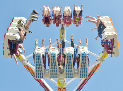 Fairgoers dangle upside down as they ride one of the fair's most popular rides, the Freak Out.