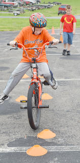 Jordan Bennett, 9, of Campbellsville, competes in the bicycle rodeo as Jonathan Vaughn, 7, of Campbellsville, looks on.