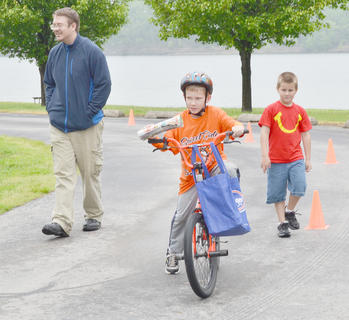 From bicycle rides and a 5K run to a special meal, Taylor County residents learned how to get fit last week. Get Fit Taylor County offered several events for residents to learn about healthy exercise and dieting. Students rode bicycles to school, residents participated in a Sweet Ride to learn about diabetes and were treated to a special meal and children competed in a bicycle rodeo. The weekend's events also included the annual I'm a Dam Runner 5K run and walk, hosted by Friends of Green River Lake. There were 306 participants this year, up from 223 last year. Proceeds collected from registration fees will benefit Friends' projects at the lake. The next Friends' event is Kids Outdoor Day on June 1.  Above, Jordan Bennett, 9, of Campbellsville, sees how well he can ride a bicycle and deliver newspapers at the same time. At left is Jordan Stapp, 4-H program assistant at Taylor County Extension Office, who coordinated the bicycle rodeo, and Jonathan Vaughn, 7, of Campbellsville.