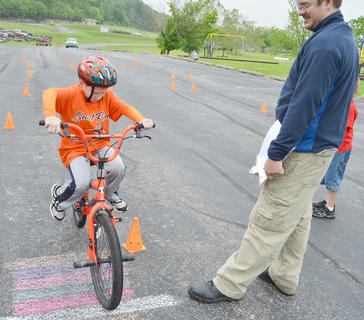 Jordan Stapp, 4-H program assistant at Taylor County Extension Office, who organized the bicycle rodeo, sees how well Jordan Bennett, 9, of Campbellsville, has scored.
