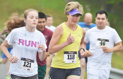 From left, Caroline McMahan, Cathy McMahan and, in back, Hector Guspar participate in Saturday's race. They came in third, first and third in their age categories, respectively.