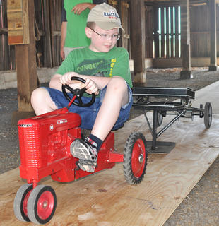 About 300 people attended the 17th annual Russell Creek/Homeplace on Green River Antique Gas Engine and Tractor Show on Saturday. Attendees were allowed an up close look at 47 tractors, most of which were manufactured in the first part of the 20th century. An obstacle course and egg run gave participants an opportunity to demonstrate the power and quality of their tractors. There was also a pedal tractor pull that several children participated in, making the show a family-friendly event for tractor enthusiasts of all ages. Located on a 200-acre historical farm, The Homeplace on Green River hosts public events throughout the year. More information about Homeplace is available at www.homeplacefarm.org. See more photos from the tractor show online at www.cknj.com.  Brett Larimore pedals hard in the pedal tractor pull at the Russell Creek/Homeplace on Green River Antique Gas Engine and Tractor Show on Saturday.