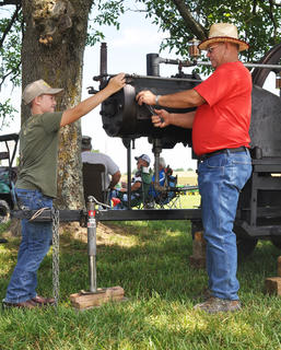 Nate Houk of Campbellsville and his grandfather, Ron Arnett of the Grab community in Green County, make sure their 100-year-old South-Penn Oil field engine is in prime condition before showing its power at the Russell Creek/Homeplace on Green River Antique Gas Engine and Tractor Show on Saturday.