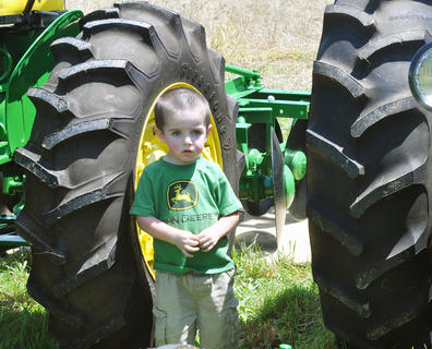 Bryce Cowherd of Campbellsville shows that a love for tractors is often inherited as he stands in front of one of the tractors owned by his grandfather Eddie Cowherd at the Russell Creek/Homeplace on Green River Antique Gas Engine and Tractor Show on Saturday.