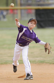 Ethan Coghill of the Rockies makes a throw to first base during a game against the Astros.