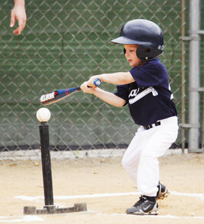 Ethan Irwin of the Braves takes a swing in tee ball action Saturday.