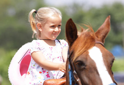 Mackenzie Driver, 4, of Campbellsville, rides Rosebud at the Taylor County Fair on Saturday.