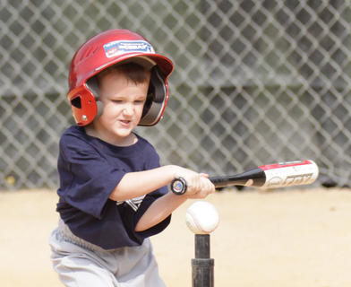 J.T. Johns of the tee ball Brewers concentrates as he smacks the ball.
