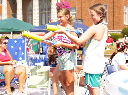 Girls on a float in the Fourth of July parade help spectators stay cool by spraying them with water.