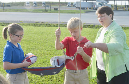 KCA fifth grade teacher Joyce West helps her students, Emily Smith and Jackson Grimsley, hang the school's flag.