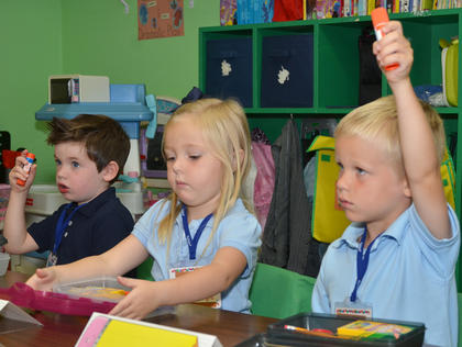 KCA preschool students, from left, Campbell Parsons, Bella Wasson and Oaks Mattingly see if they have all their school supplies ready for class.