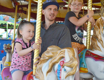 Children enjoy the merry-go-round.
