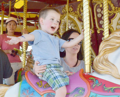 Melissa Osmun of Campbellsville holds her son, Ace, 3, as they ride the merry-go-round.
