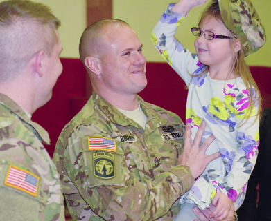 Sgt. 1st Class Robbie Rogers' daughter Jaci, 4, tries on her dad's hat. Rogers, of Campbellsville, is one of 14 Campbellsville National Guard soldiers who have been deployed to the Middle East for about nine months.