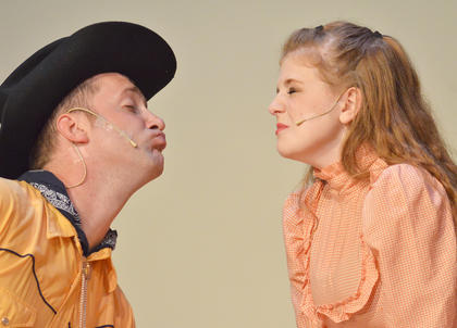 Will Parker, portrayed by Chad Shively of Campbellsville, puckers up for a kiss from his love, Ado Annie, played by Carrie Fowler.