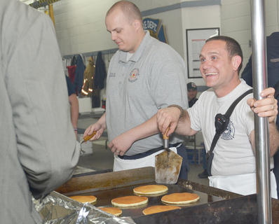 Wes Dillon, at left, and Keith Bricken talk with a customer as their pancakes cook.