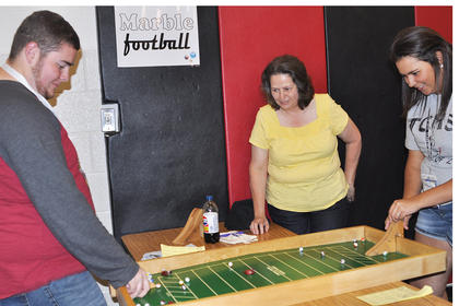 Volunteer Nancy Buckman watches Christopher Wilson and Samantha Buckman try to beat each other at marble football TCHS Project Graduation on May 24.