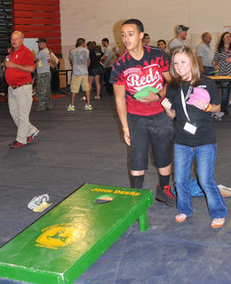 Natalie Sluder shows her excitement as her teammate Casey Seaborne sinks one in while playing cornhole at TCHS Project Graduation on May 24.