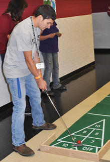 Dylan Skaggs tests his golf skills while playing shuffle putt at TCHS Project Graduation on May 24.