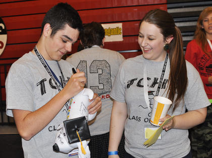 Wes Phillips is one of the first to sign Jenna Corbin's graduation puppy keepsake at TCHS Project Graduation on May 24.
