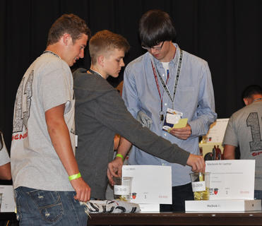 From left, Jared Peake, Wade Clark and Chace Pruyear place bids for the silent auction at TCHS Project Graduation on May 24.