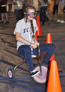 Wearing alcohol simulation goggles, Macayla Bertram struggles to pedal through an obstacle course at TCHS Project Graduation on May 24.