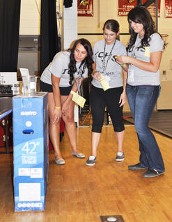From left, Emily White, Erika Gaddie and Mariah Malone check out the features of a 42-inch flat screen TV, one of several prizes that graduates competed for at TCHS Project Graduation on May 24.