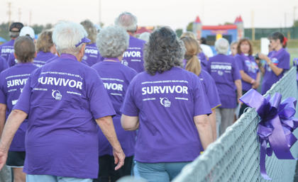 Survivors, wearing matching T-shirts, ban together to take the first lap of the night.