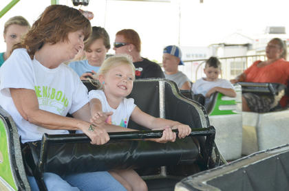 Paty Confer, at left, and Kourtlyn Confer, of Lebanon, smile as they are on a ride at the fair.