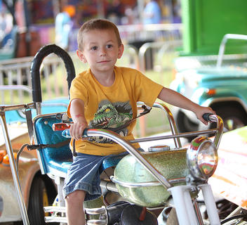 A young boy enjoys being on a motorcycle on the carousel at the Taylor County Fair on Monday.
