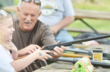 Barry Eastridge of Campbellsville helps Amber Mittchell of Lawrenceburg shoot a pellet rifle.